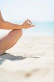 Closeup på den unga kvinnan som gör yoga på stranden Arkivfoton