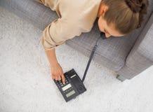 Closeup på den unga kvinnan som lägger på soffan och det ringande telefonnumret Fotografering för Bildbyråer
