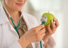 Closeup på doktorn som använder stetoskopet på äpplet Royaltyfri Bild