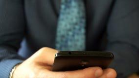Closeup på en affärsman som bläddrar meddelanden på hans sista utvecklingssmartphone lager videofilmer