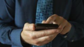Closeup på en affärsman som bläddrar meddelanden på hans sista utvecklingssmartphone stock video