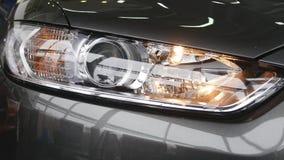 Closeup på en billykta av ett mörker - grå bil lager videofilmer