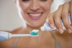 Closeup på händer som pressar toothpaste på borste royaltyfria foton