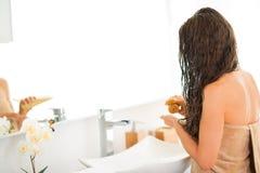 Closeup på kvinnan som applicerar hårmaskeringen i badrum Arkivbild