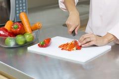 Closeup på kvinnan som klipper nya grönsaker Royaltyfri Bild