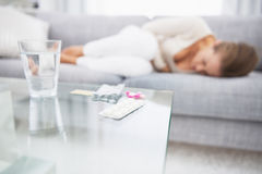 Closeup på medicin på tabellen och dålig kvinna för känsla i bakgrund Royaltyfria Foton