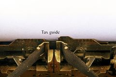 Closeup på tappningskrivmaskinen Främre fokus på bokstäver som gör SKATT ATT VÄGLEDA text Affärsidébild med det retro kontorshjäl arkivfoton