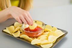 Closeup på tonåringflickan som äter chiper royaltyfri bild