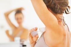 Closeup på kvinnan som applicerar på rulldeodoranten underarm Arkivfoto