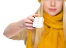 Closeup on pack of pills in hand of young woman in hat and scarf Stock Photography