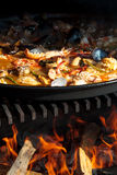 Closeup Paella over open fireplace. Cooking and making a traditional Spanish Paella over open fire with fire wood and coal. Made from chicken and seafood in Royalty Free Stock Photos