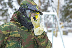 Closeup of paintball player in mask with paint splash showing pe Stock Photography