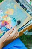 Closeup of paintbrush in woman hands mixing paints on palette outdoor. Closeup of paintbrush in woman hands mixing paints on palette royalty free stock photos