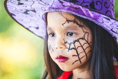 Closeup on painted face of asian child girl on Halloween celebration