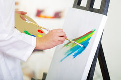 Closeup painters hands using brush on canvas applying colorful art to white background.  Royalty Free Stock Images