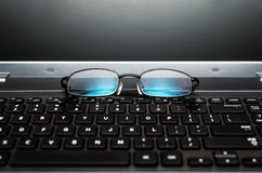Closeup pair of glasses on the laptop keyboard stock images