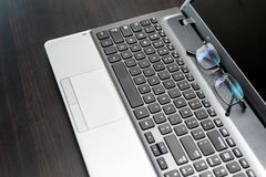 Closeup pair of glasses on the laptop keyboard Stock Photography