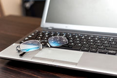 Closeup pair of glasses on the laptop keyboard Royalty Free Stock Images