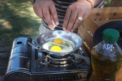 Closeup of a pair of hands cracking an egg into a pan stock images
