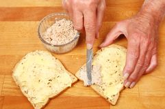 Hands making a sandwich. Closeup of a pair of hands making a tuna mayonnaise sandwich royalty free stock images