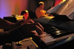 Closeup of pair of hands playing a piano in concert. Closeup of a pair of hands playing a piano in concert royalty free stock photo