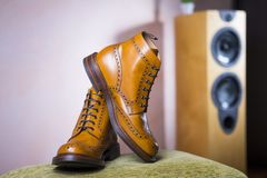 Closeup of Pair of Mens Tanned Semi-Brogue Boots on One Another. Indoors. Against of Floorstanding Loudspeaker on Background.Horizontal Image Composition Royalty Free Stock Photo