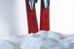 Closeup of A Pair of Skis Behind Heap of Snow. Closeup of a pair of red skis behindi a heap of artificial snow stock photo