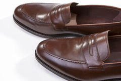 Closeup of Pair of Stylish Brown Penny Loafer Shoes Against White Stock Images