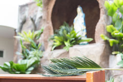 Closeup of palm leaf on pews with de-focused grotto Stock Photos