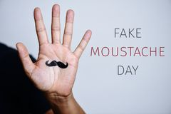 Moustache in a hand and text fake moustache day royalty free stock photos
