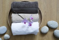 Closeup of pampering towels and zen stones for female bodycare. Closeup of pampering towels and zen stones on round wooden background for concept of pure Royalty Free Stock Photo
