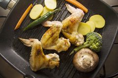 Closeup of Pan with grilling foods. Chicken legs and wings on a grill pan on white Royalty Free Stock Images