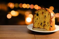 Closeup panettone on ceramic plate on wooden table, bokeh background with lights. Front view Stock Image