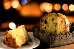 Closeup panettone inside box on wooden table, bokeh background with lights. Front view Royalty Free Stock Photos