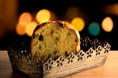 Closeup panettone inside box on wooden table, bokeh background with lights. Front view Stock Photo