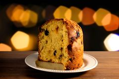 Closeup panettone inside ceramic dish on wooden table, bokeh background with lights. Front view Royalty Free Stock Photos