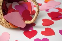 Paper heart falling from wooden basket on white background - valentine`s day concept. Closeup of paper heart falling from wooden basket on white background royalty free stock photo