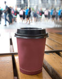 Closeup of a paper plastic coffee cup. Red paper coffee cup with blurred urban background Stock Photography