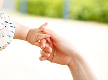 Closeup parent and baby holding hand together Stock Images
