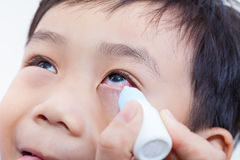 Closeup of parent pouring eye drops in eye her son Royalty Free Stock Image
