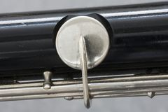 Closeup of part of bass clarinet with grey background. Closeup of part of bass clarinet with gray background Stock Image