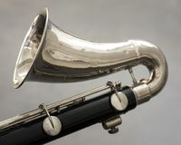Closeup of part of bass clarinet with grey background. Closeup of part of bass clarinet with gray background Royalty Free Stock Photo