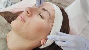 Closeup part of face depilation of eyebrows with a thread. Permanent tattooing of eyebrows. stock footage
