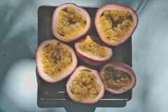 Closeup the passionfruit in plate on the color table. Royalty Free Stock Image