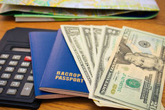 Closeup of a passport, calculator and dollars. Map in the background. Stock Photos