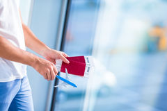 Closeup passports and boarding pass at airport in male hands Royalty Free Stock Images