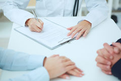 Closeup of patients hands and doctor taking notes. Royalty Free Stock Image