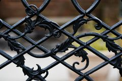 A closeup of a pattern in a cast metal gate. A closeup of the detail in a cast iron gate in front of an old church royalty free stock photography