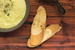 Closeup Pea soup with bread on rustic wooden table, top view royalty free stock photography