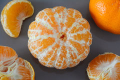 Closeup of peeled and unpeeled whole mandarin and pieces on a grey background Stock Photos